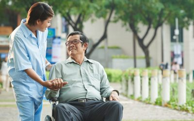 Nurse talking to senior Asian man in wheelchair
